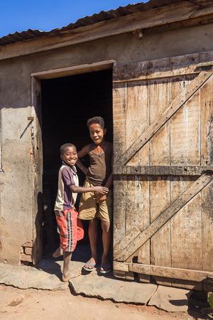 gente pobre: BELO SUR TSIRIBIHINA, MADAGASCAR, 03 de julio: los ni�os africanos no identificados en la puerta de una casa tradicional en 03 de julio 2006 en el t�pico pueblo de Belo sur Tsiribihina, Madagascar occidental