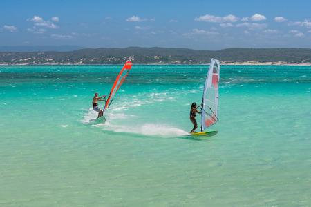 windsurf: Pareja de amantes del windsurf en la inmensidad de la laguna