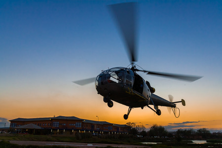 Helicopter landing at sunset to the heliport