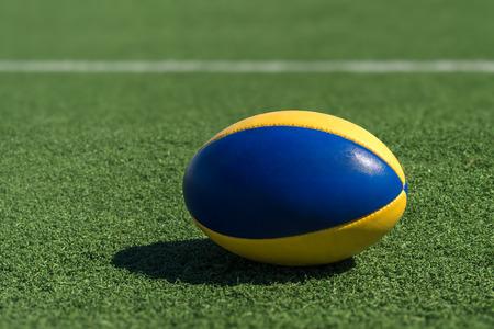 pasto sintetico: Una pelota de rugby en un césped sintético en frente de la línea blanca.