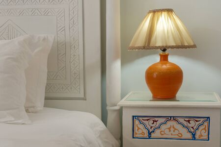 modern apartment: A lamp on a nightstand next to a bed with a white carved headboard Stock Photo