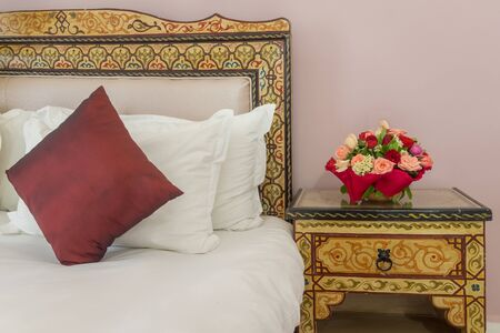 honeymoon suite: A bouquet of flowers on a bedside table next to a bed with a painted headboard Stock Photo