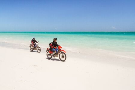 Two bikers riding on the white sand beach of the Ambatomilo lagoon, south of Madagascar on october 24, 2016