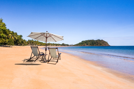 Tropical virgin beach with loungers and umbrella in Nosy Be, Madagascar