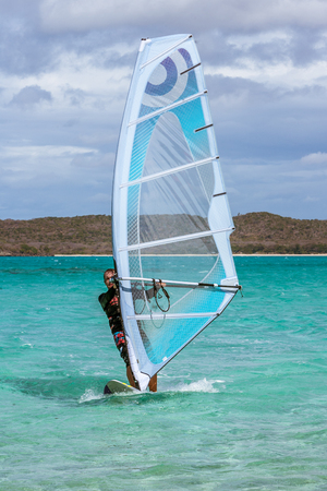 sailboard: Mens windsurfer surfing in the lagoon