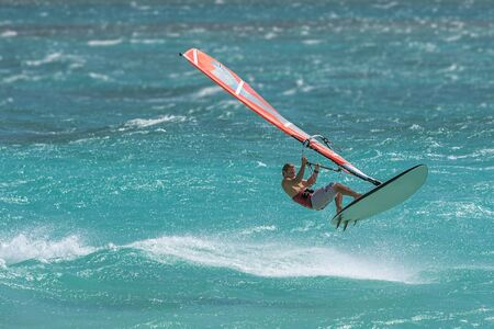 sailboard: Professional windsurfer jumping in the waves