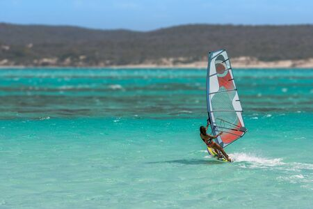 sailboard: Womens windsurfer surfing in the lagoon