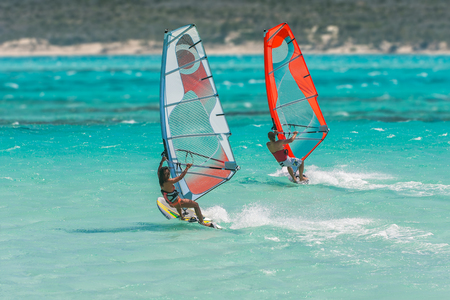 Couple windsurfers in the lagoon of Emerald Sea, Antsiranana bay (Diego Suarez), Madagascar. Banco de Imagens
