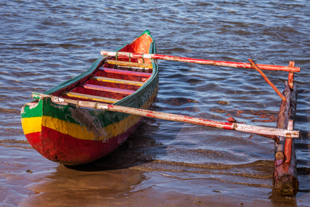 Outrigger canoe rasta colored on the beach of Foulpointe, eastern Madagascar