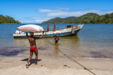 Mahalevona, Madagascar, April 23, 2017: People loading goods in a boat in the Antongil bay, East of Madagascar Editorial