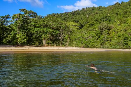 bather: Antalavia, Madagascar, April 20, 2017: Swimmer on Antalavia beach in front of Masoala forest, Antongil bay, Madagascar
