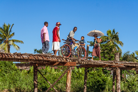 Maroantsetra, Madagascar, April 22, 2017: Malagasy people walking on the wooden bridge in Maroantsetra, East of Madagascar