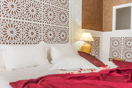 Beautiful hotel bedroom with a carved headboard in arabic style