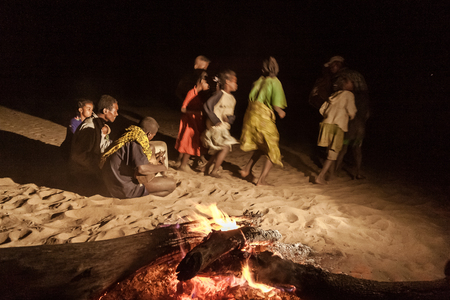 Malagasy villagers and their makeshift musical instruments dancing near the wood fire at dusk on the banks of Tsiribihina river, Madagascar
