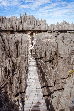 Tsingy de Bemaraha National Park, Madagascar, July 02, 2017: Tourists hikers on the wooden footbridge of Tsingy de Bemaraha Sajtókép