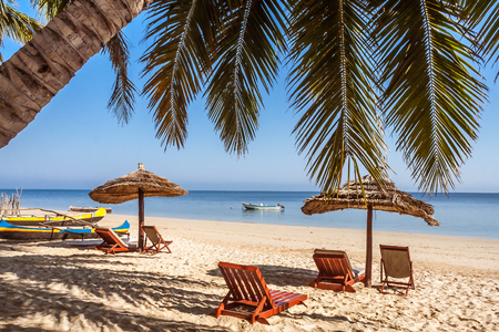 Sunbeds and deckchairs under the palm tree on Ifaty beach, southwest Madagascar Stock Photo