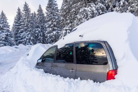 Car almost totally buried under a snow at the alpin ski station