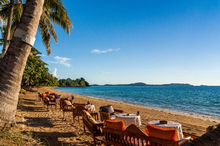 Wooden tables with armchairs and benches at a luxury resort close to a tropical beach