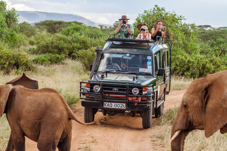 Masai Mara, Kenya, May 19, 2017: Tourists in an all-terrain vehicle exploring the African savannah on safari game drive Publikacyjne