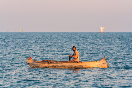 Ifaty, Madagascar, June 15, 2017: Malagasy fishermen rowing their traditional outrigger canoe in the lagoon of southwestern Madagascar