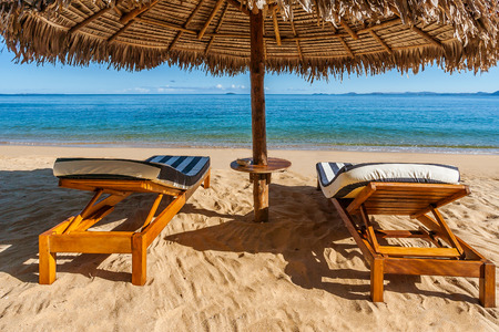 Two sunbeds under a thatched umbrella on the beach in front of a calm sea Banque d'images