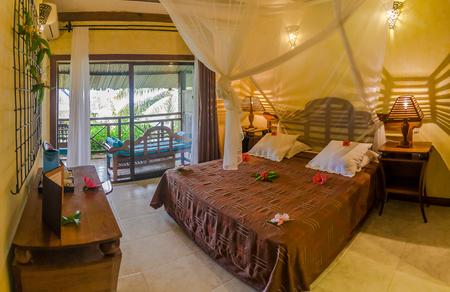 Luxury tropical hotel room with precious wood furniture