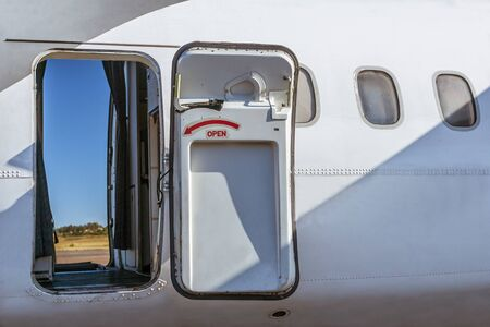 Open door of an aircraft with a view of the runway