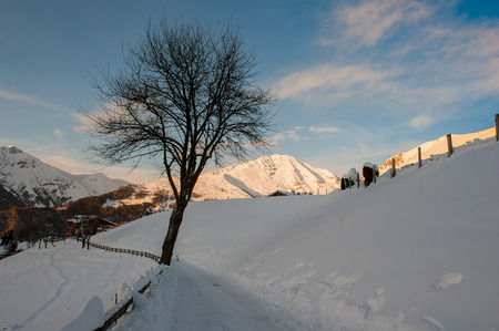 mountain village covered with snow at the end of the day Stock Photo