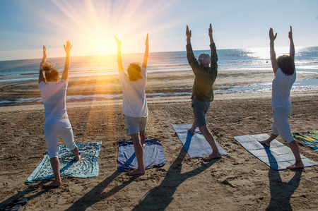 A group of people yoga in the beach Stock Photo