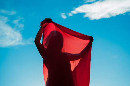 woman wrapped in a red scarf in the wind