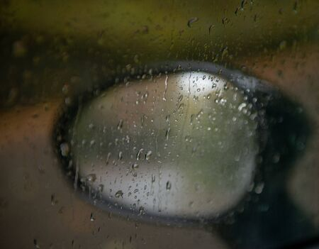 rear view mirror of car wet from drops of water