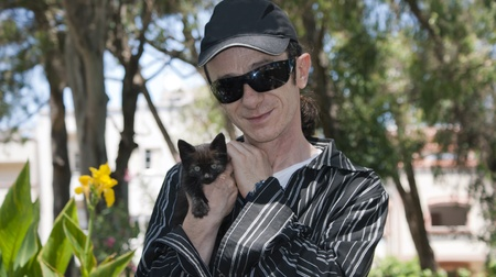 man with a black kitten in her arms
