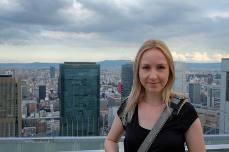 blonde girl in front of Osaka Skyline