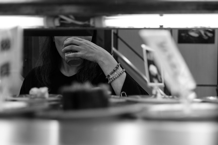 woman in Sushi restaurant drinking green tea