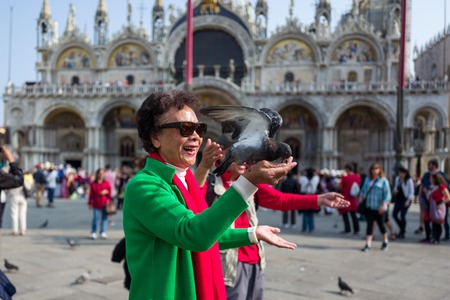 Venice - October 04: Unknown Asian tourist has fun with pigeons on the Piazza San Marco on October 04, 2017 in Venice