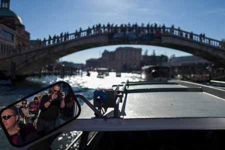 Venice - October 07: Photographer Pierre Aden makes photo of mirror with Ponte dellAccademia and tourists in background