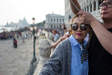 Venice - October 04: Unknown Asian tourists make a selfie in front of the famous Ponte dei Sospiri bridge on October 04, 2017 in Venice Editorial