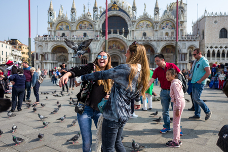 Venice - October 04: Unknown female tourists have fun with pigeons on the Piazza San Marco on October 04, 2017 in Venice Editorial