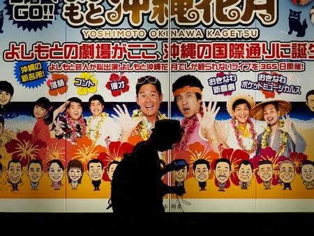 Naha, Japan - November 19: Unknown boy walks in front of advertising on November 19, 2015 in Naha, Japan