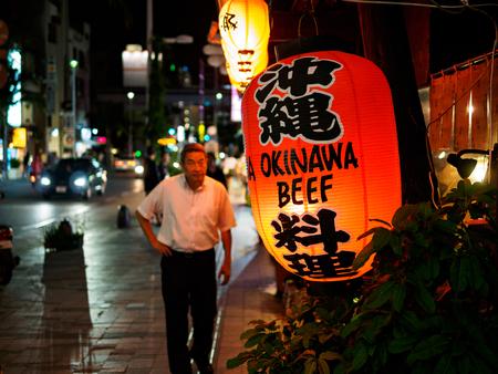 Naha, Japan - November18: Unknown man walks on the streets in front of Okinawa Beef lantern on November 18, 2015 in Naha, Japan