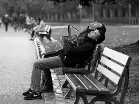 Frankfurt, Gemany - October 24: Unidentified men sleep on bench at the lake on October 24, 2015 in Frankfurt, Germany.
