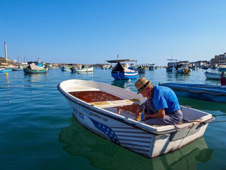 Marsaxlokk, Malta: October 08: Unidentified old man prepares fisher boat on October 08, 2014 in Marsaxlokk, Malta.