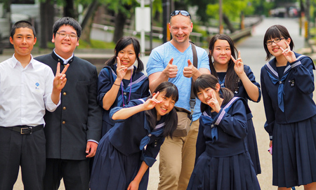 Nara, Japan - May 14: Photographer Pierre Aden poses with Japanese students for a photo on May 14, 2014 in Naha, Japan