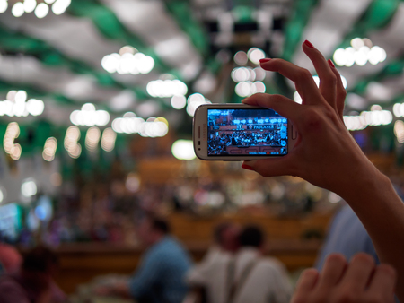 Munich, Germany - September 21: Unidentified girl makes photo of tent on the Oktoberfest with her mobile phone on September 21, 2015 in Munich, Germany.