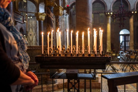 Venice, Italy - October 05: Unidentified woman prays next to candles in Basilica di San Marco on October 05, 2017 in Venice, Italy. Editorial