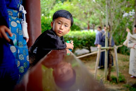 Naha, Japan - November 19: Young boy in traditional clothes in park looks at camera on November 19, 2015 in Naha, Japan.
