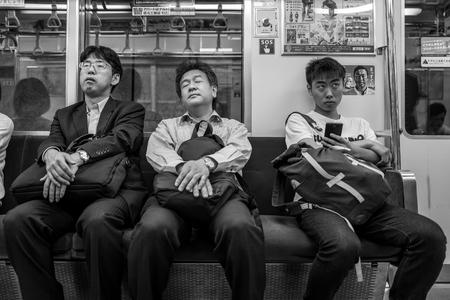 Fukuoka, Japan - May 19: Unidentified tired men in a tram on May 19, 2017 in Fukuoka, Japan.