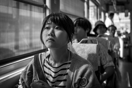 Kumamoto, Japan - May 13: Young girls sits in tram on May 13, 2017 in Kumamoto, Japan.