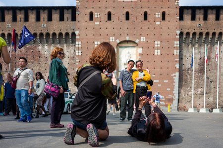 Milan, Italy - September 28: Unidentified Asian tourists make photos in front of Castello Sforzesco on September 28, 2017 in Milan, Italy.
