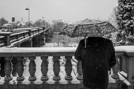 Hintere Ansicht des Mannes mit Regenschirm in schneebedecktem Frankfurt Standard-Bild